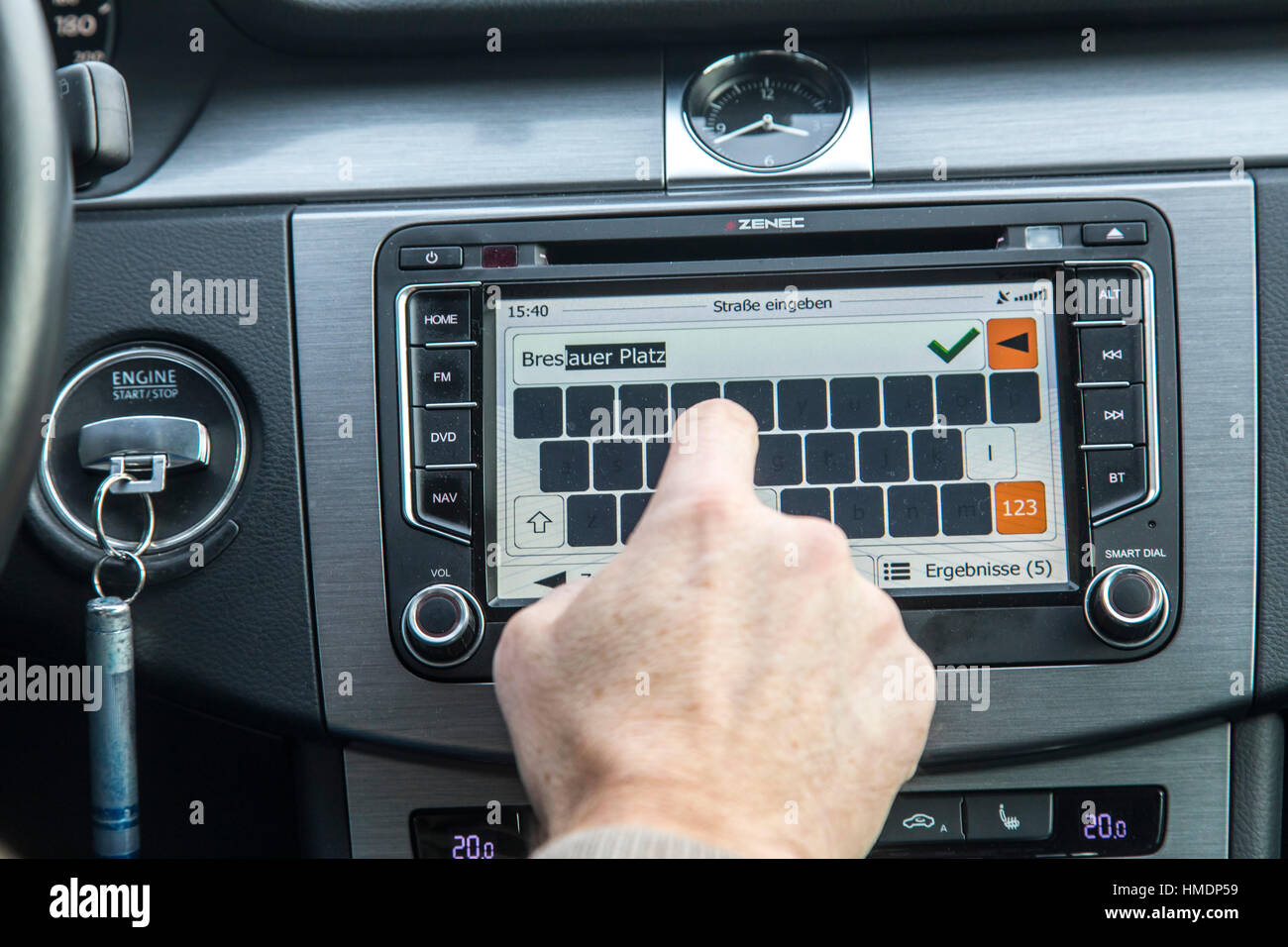 A car driver is using the cars navigation system,  while driving the car, - Stock Image