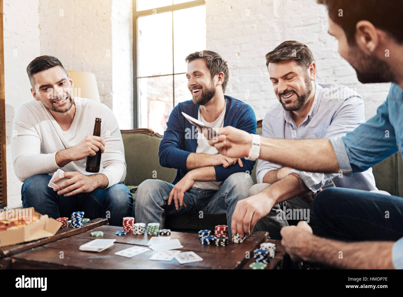 Cheerful pleasant men playing the poker game - Stock Image