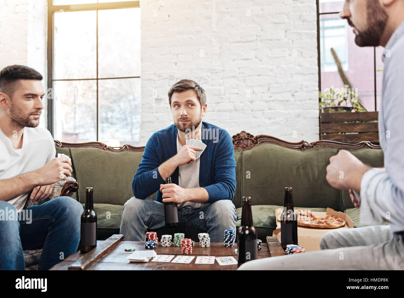 Handsome good looking man hiding his cards - Stock Image