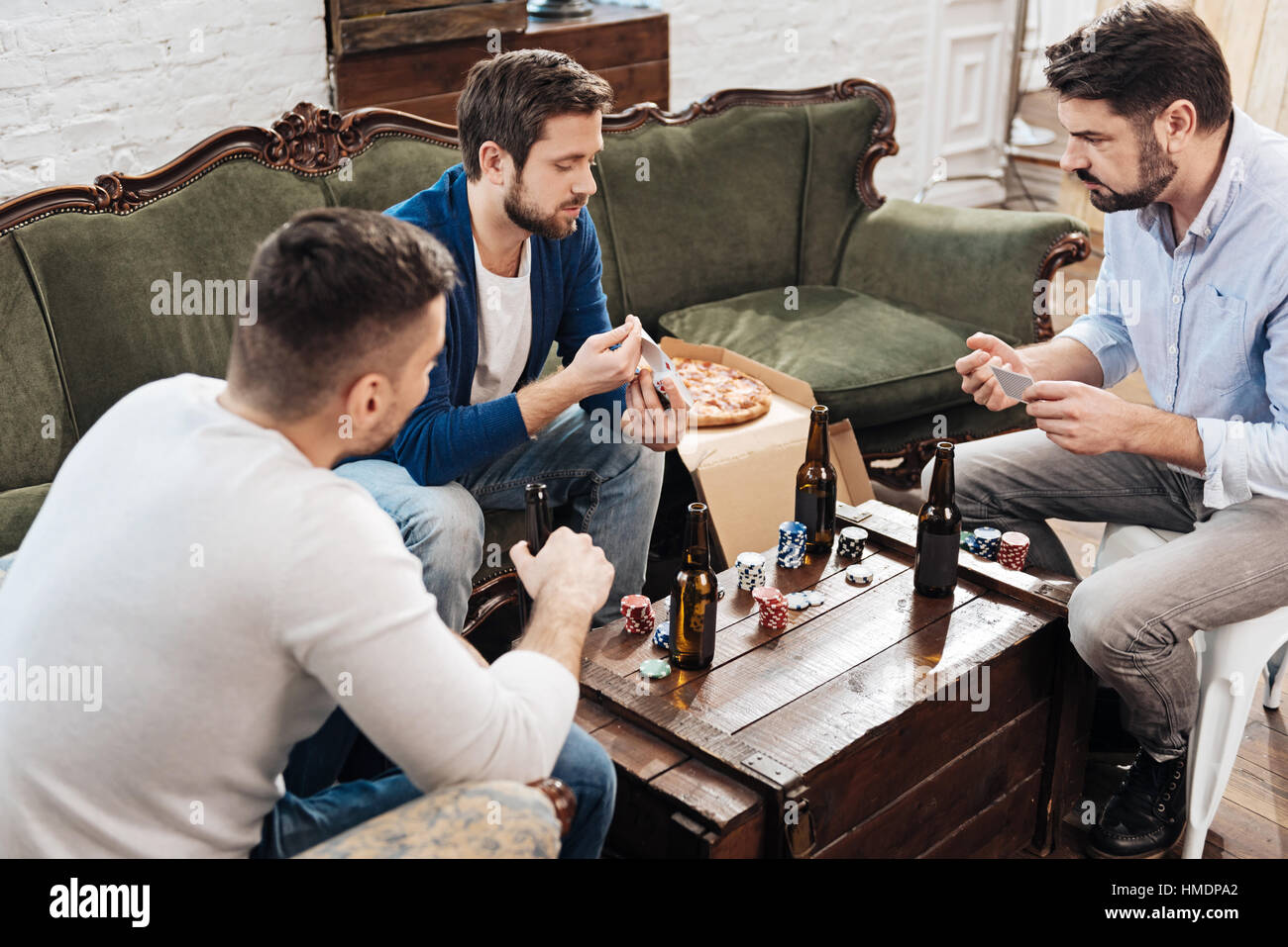 Serious handsome man shuffling cards - Stock Image