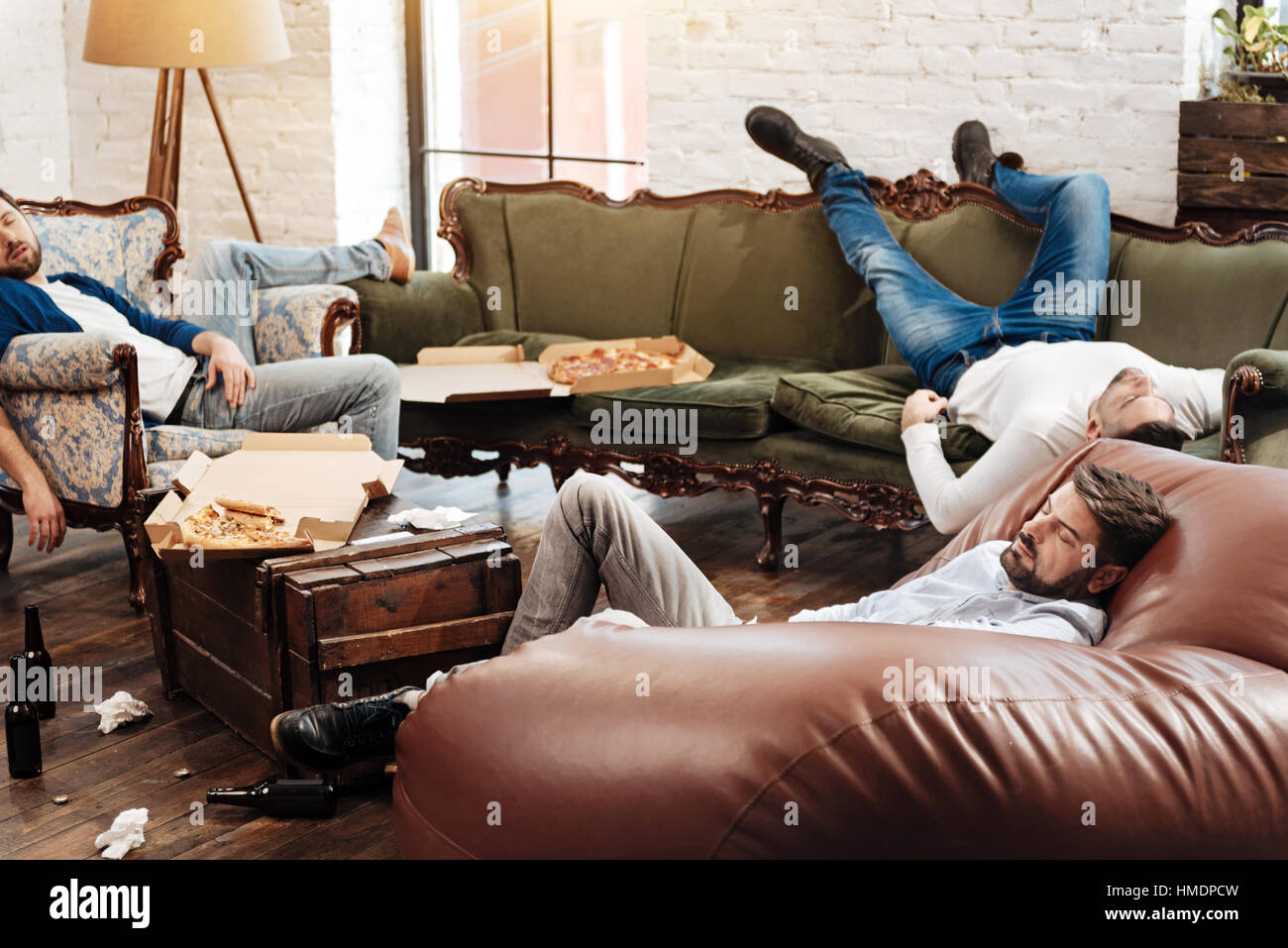 Tired bearded man resting after a bachelors party - Stock Image