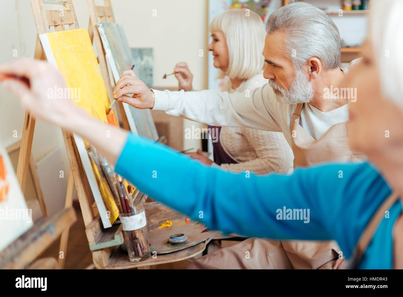 Three concentrated artists spending time in painting studio - Stock Image
