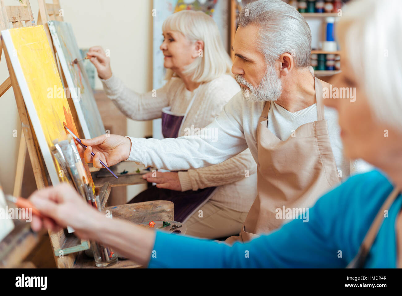 Three professional artists spending time in painting studio - Stock Image