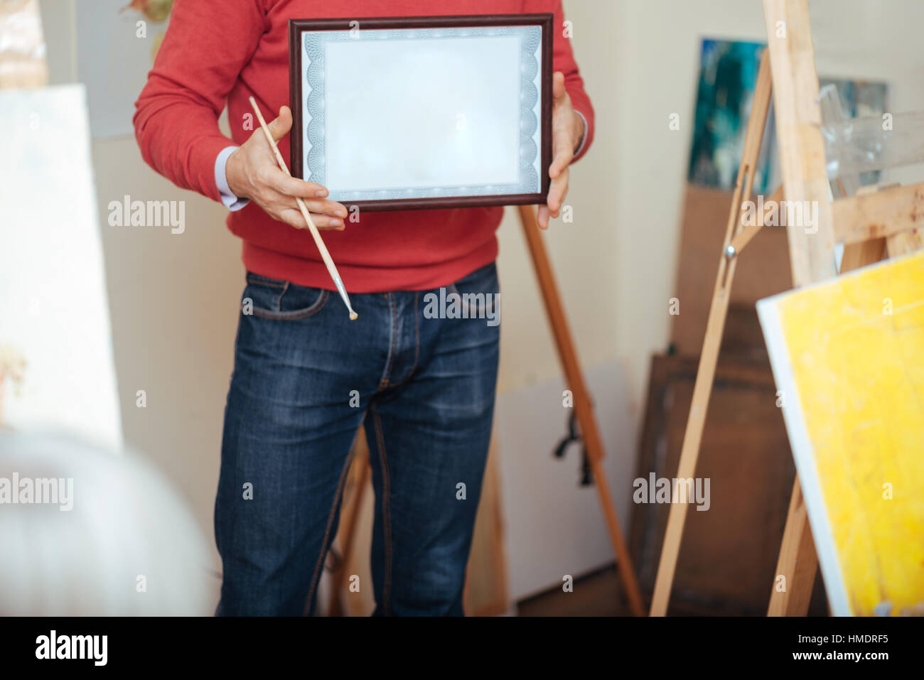 Close up of young man demonstrating a painters diploma - Stock Image