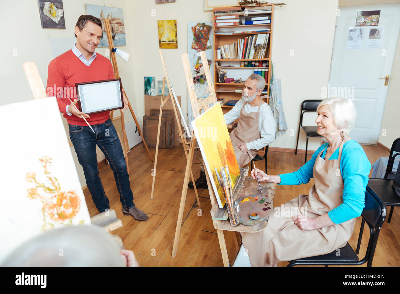 Young man demonstrating a painters diploma - Stock Image
