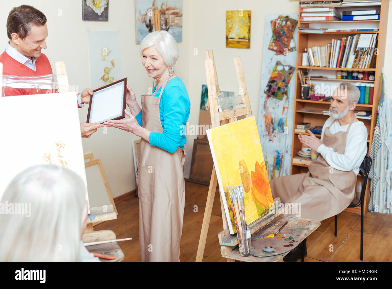 Young man giving artists diploma to woman - Stock Image