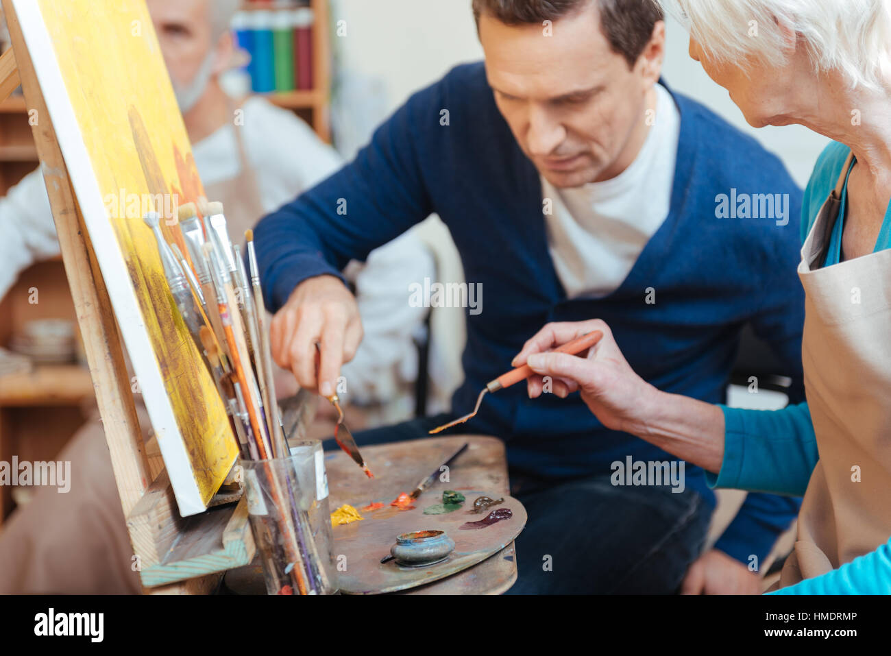 Delighted artist helping elderly woman in painting - Stock Image