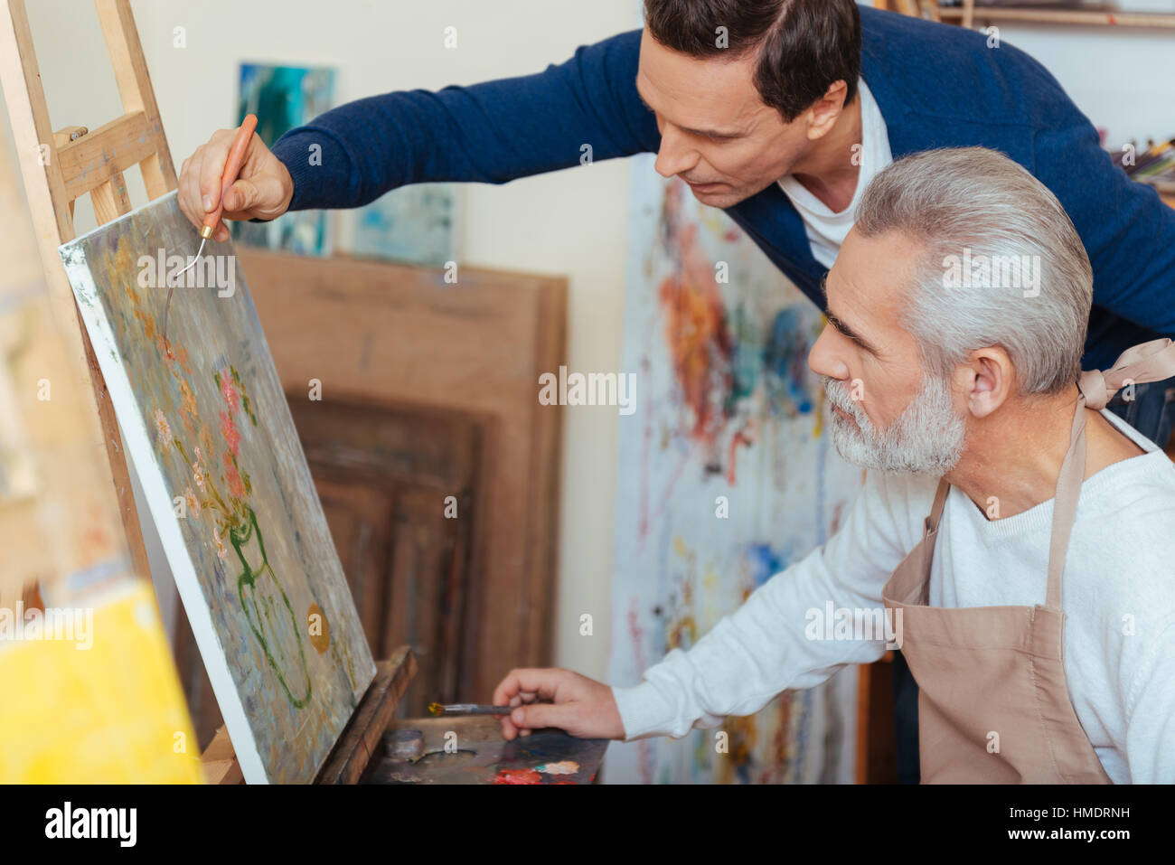 Concentrated artist helping elderly man in painting - Stock Image