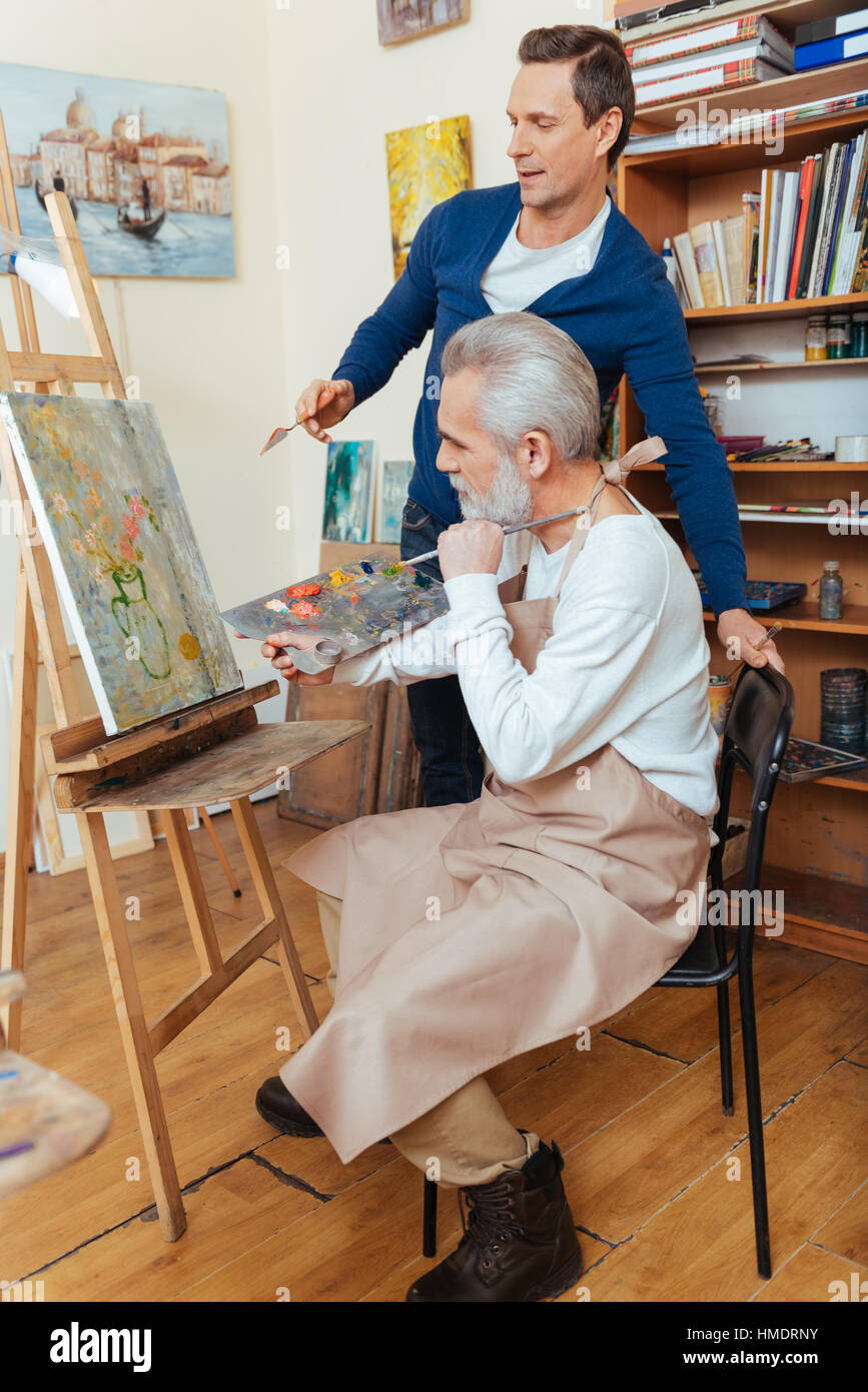 Ambitious artist helping elderly man in painting - Stock Image