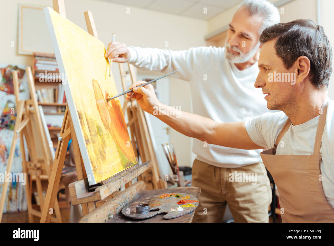 Inspired artist painting with his young colleague. - Stock Image