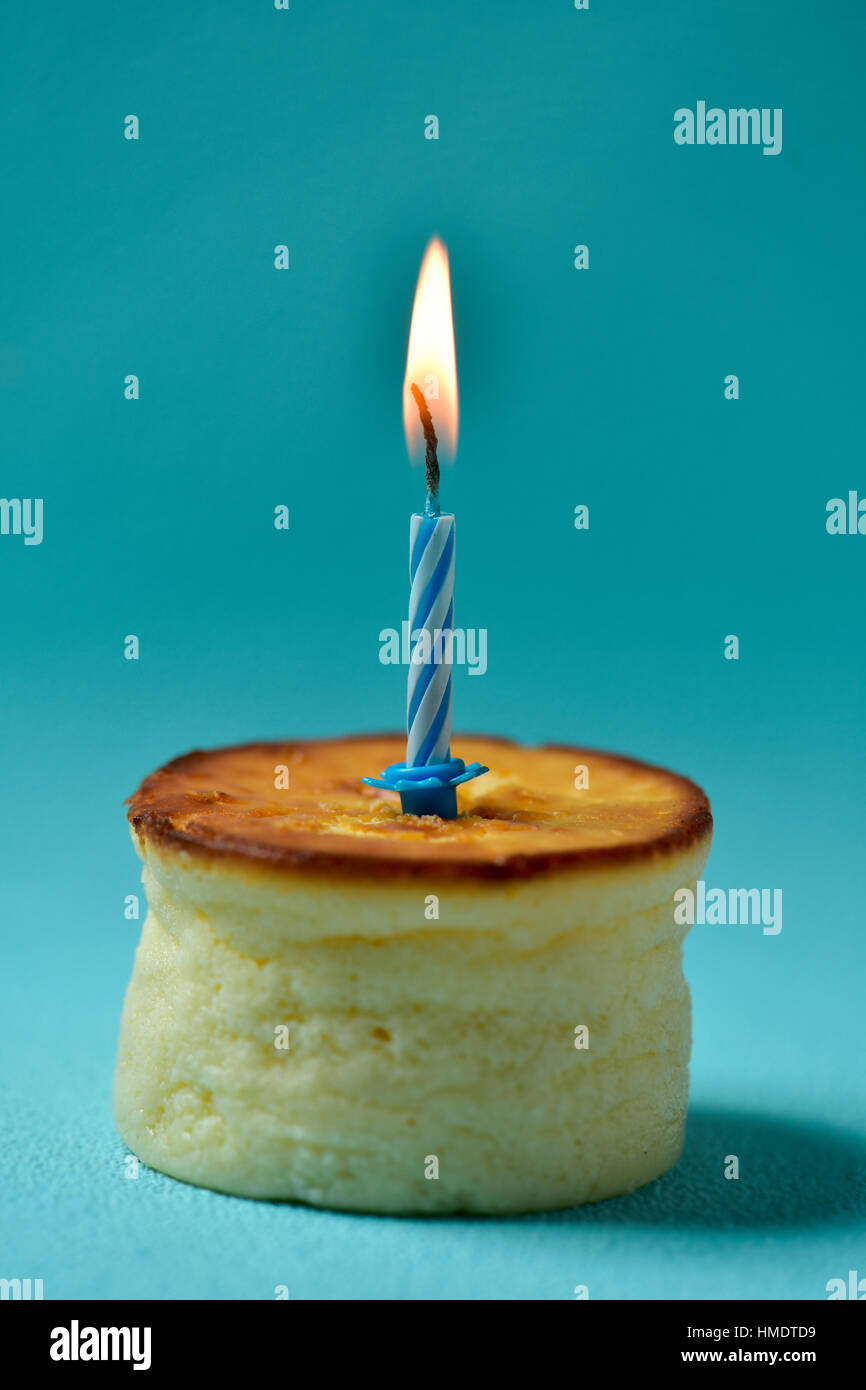 A Cheesecake Topped With Lit Birthday Candle On Blue Background