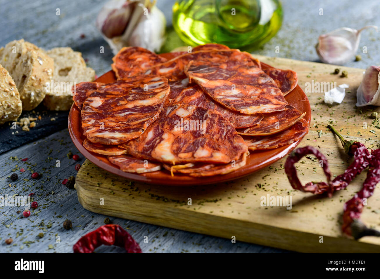 closeup of an earthenware plate with some slices of spanish chorizo, cured pork sausage, some slices of bread, a - Stock Image