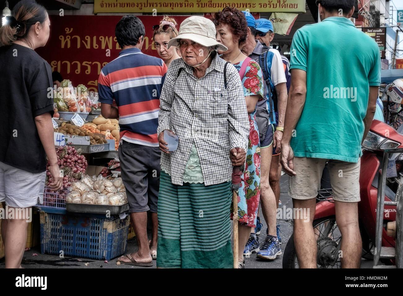 Elderly shoeless Thai woman beggar on the streets. Pattaya Thailand Southeast Asia - Stock Image