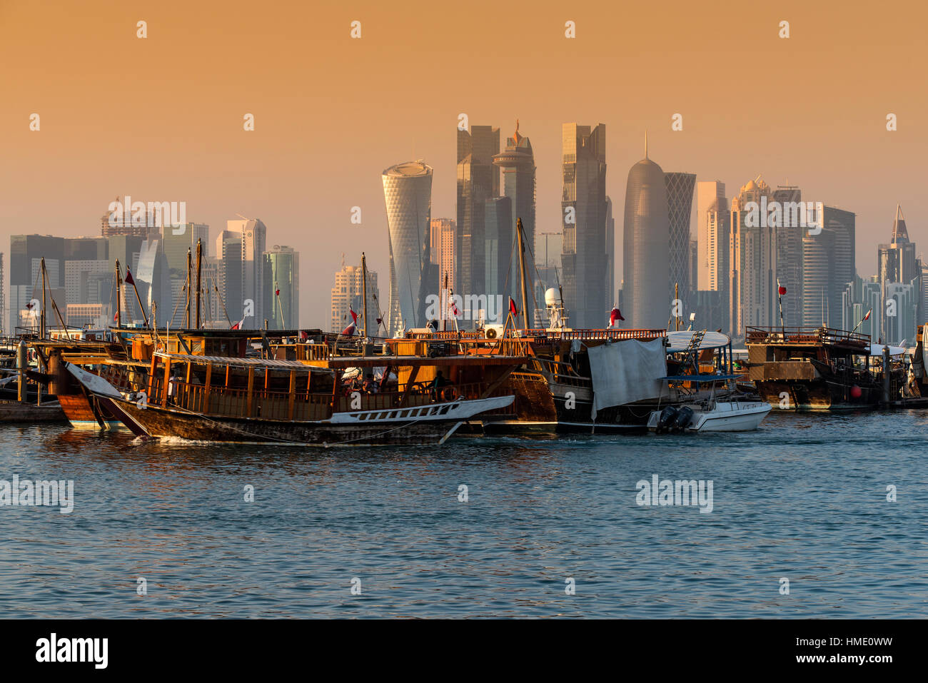 Dhow traditional sailing vessel with the financial area skyline behind, Doha, Qatar - Stock Image