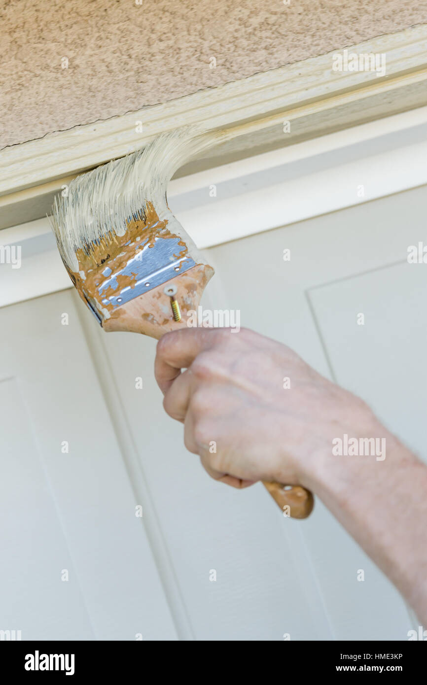 Professional Painter Cutting In With A Brush to Paint Garage Door ...