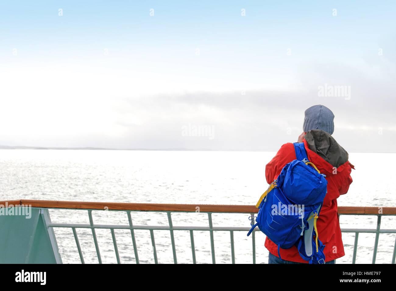 Passenger on deck of ship across Møre og Romsdal county, Norway. - Stock Image