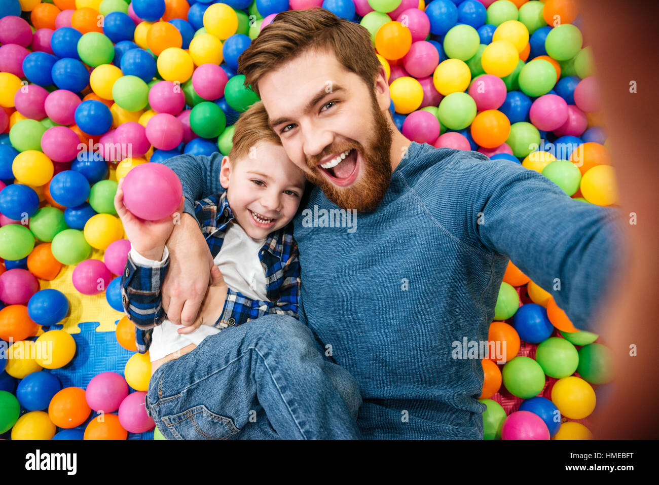 Cheerful bearded dad and little son talking selfie at pool with colorful balls Stock Photo