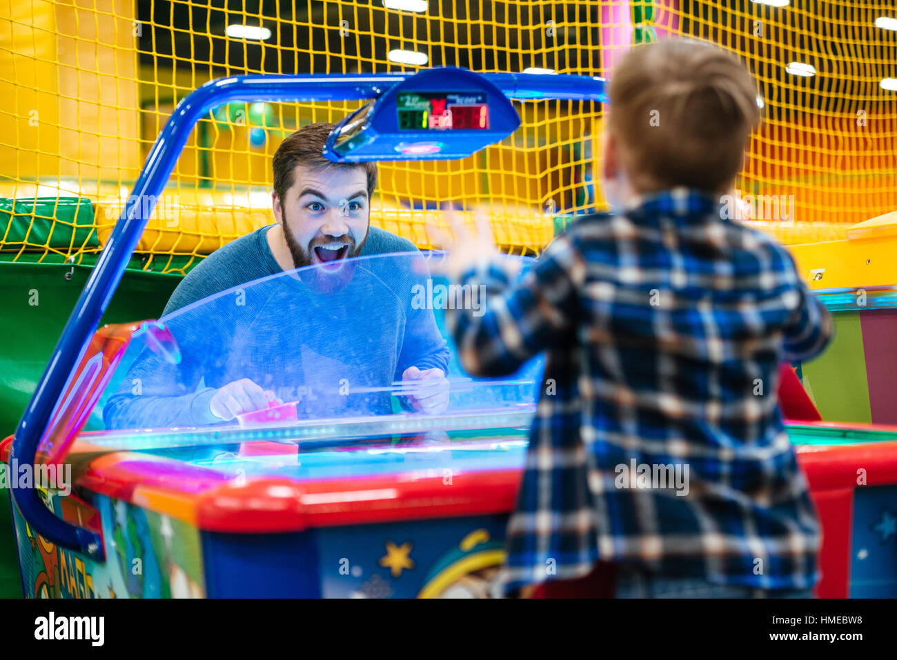 Joyful bearded father and son playing air hockey game at amusement park Stock Photo