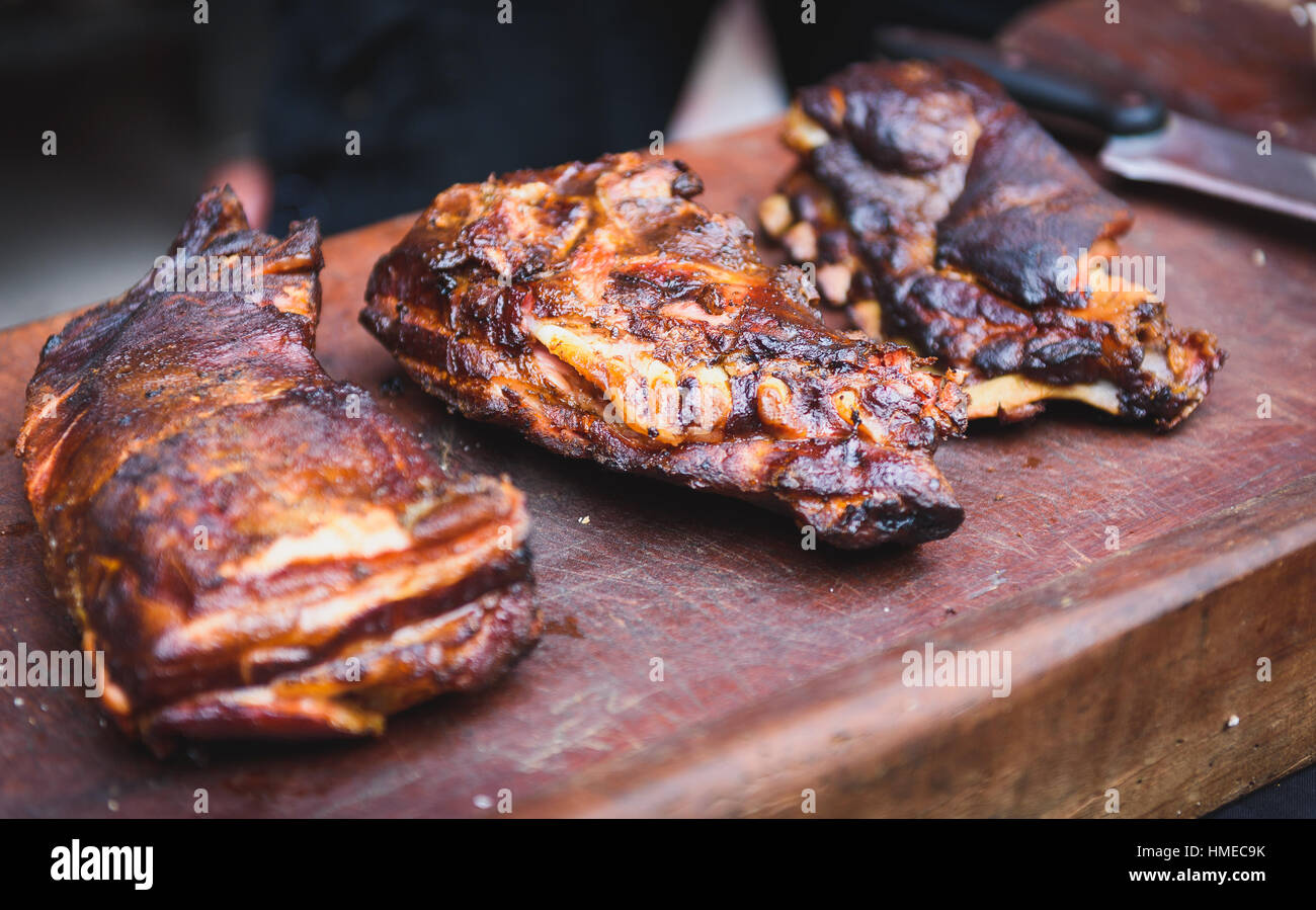 Grilled spare beef or pork back ribs prepared in smoker. Delicious roasted cuts of meet made on barbecue smoker - Stock Image
