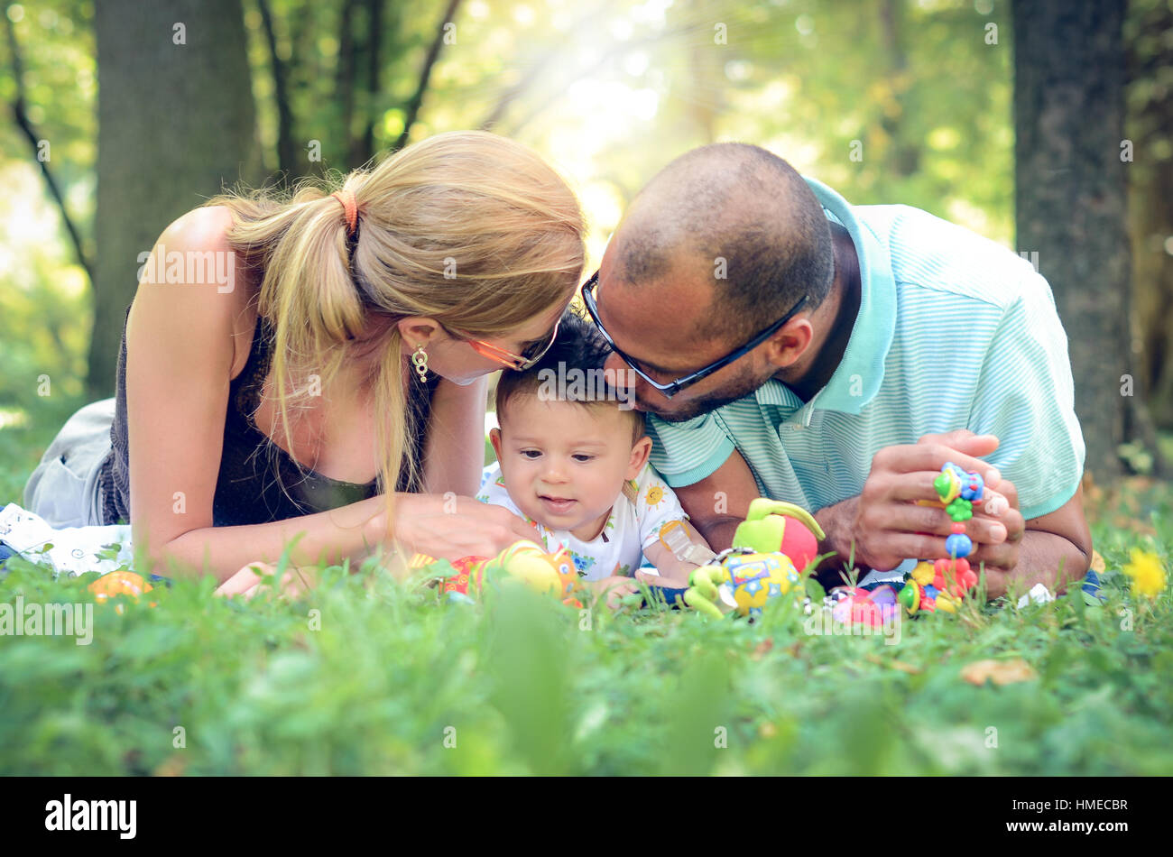 Happy interracial family is enjoying a day in the park. Little mulatto baby boy.  Parents are kissing their child - Stock Image