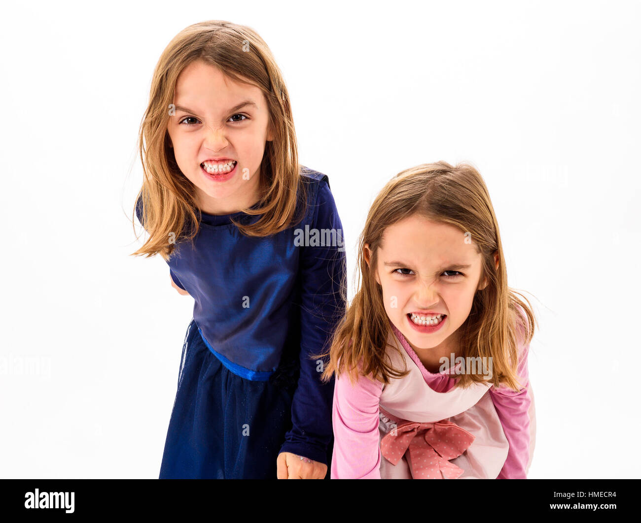 Twin girls are angry, mad and disobedient with bad behavior. Children making the act of insubordination and disobedience, - Stock Image