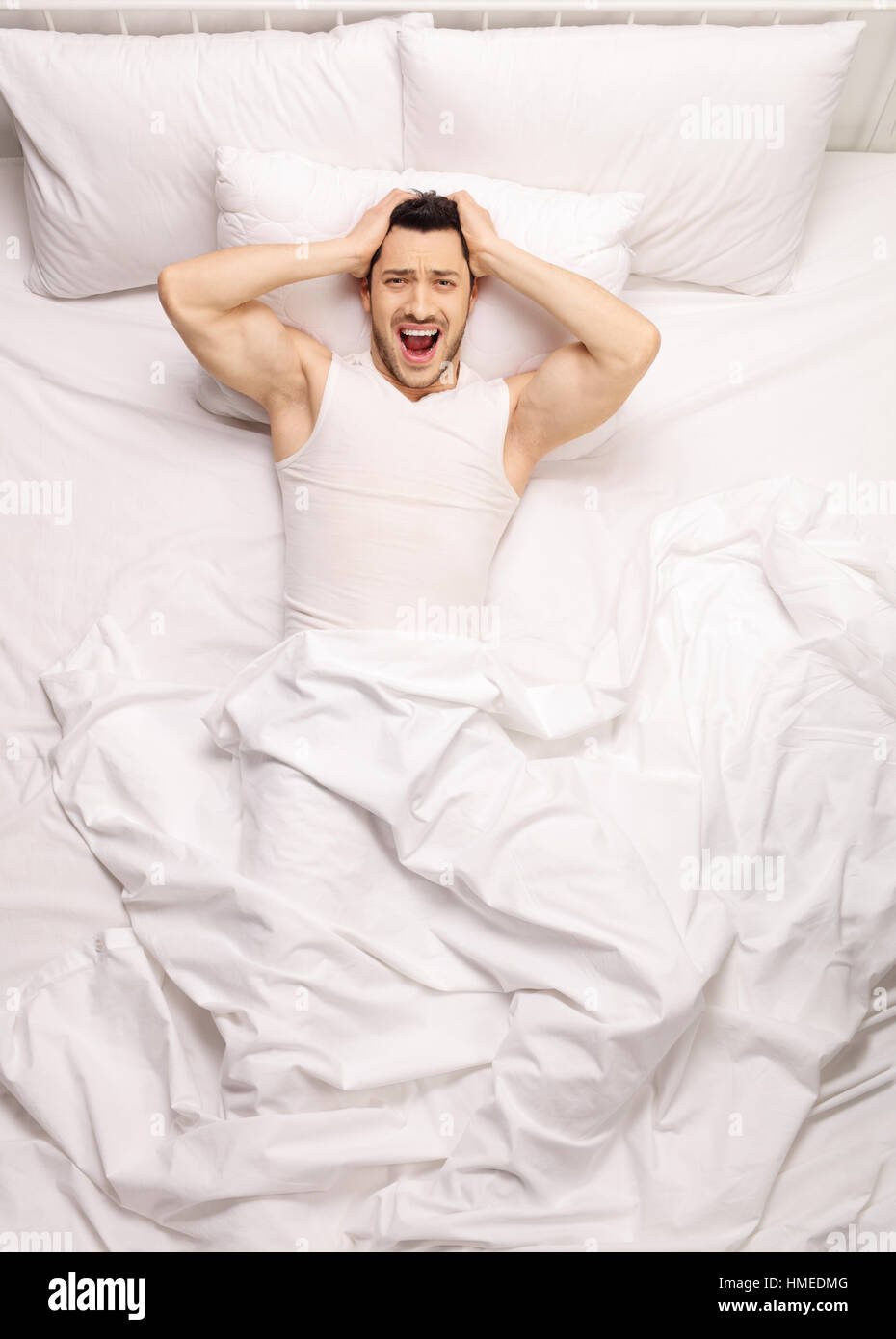 Frustrated guy lying in bed and screaming - Stock Image
