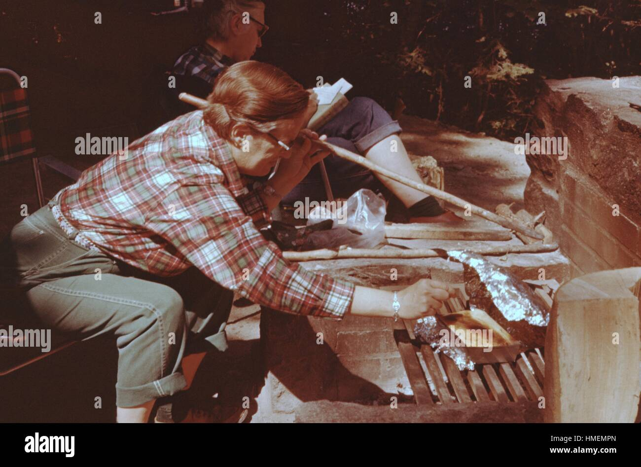 Person reaching towards a dish of food cooked over a charcoal grill during a cooking, holding a stick, Maidstone - Stock Image