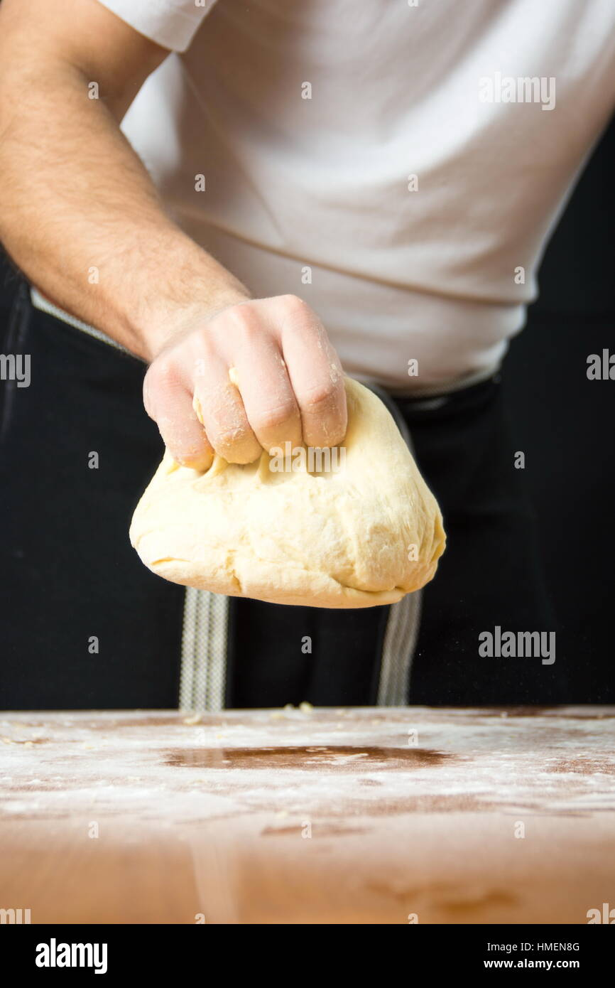 Male baker punching dough from the kitchen table - Stock Image