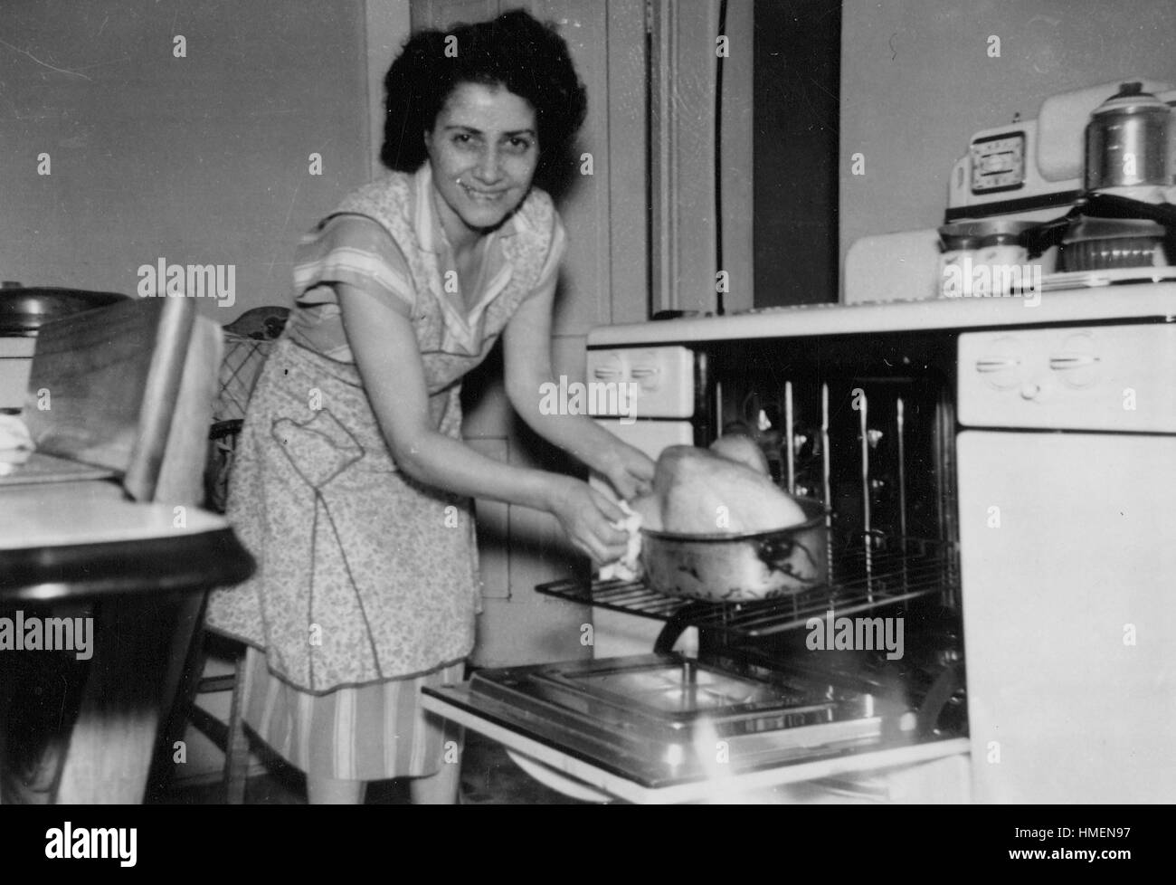 Thanksgiving day, a young woman in an apron standing in her kitchen and placing a turkey on a roasting pan into - Stock Image