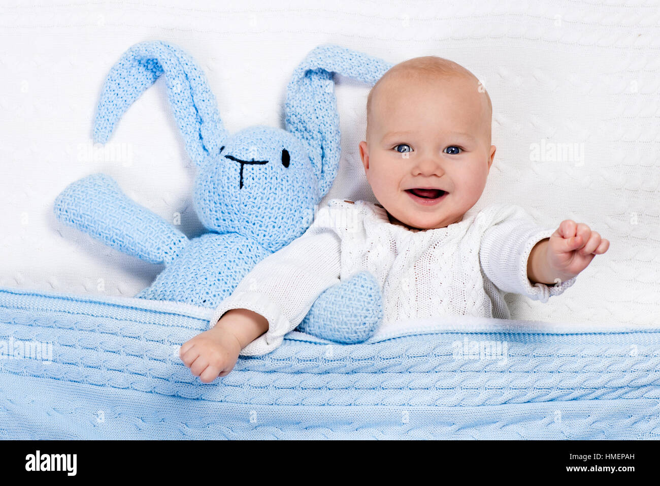 119ff99f11d4 Funny little baby wearing a warm knitted jacket playing with toy ...