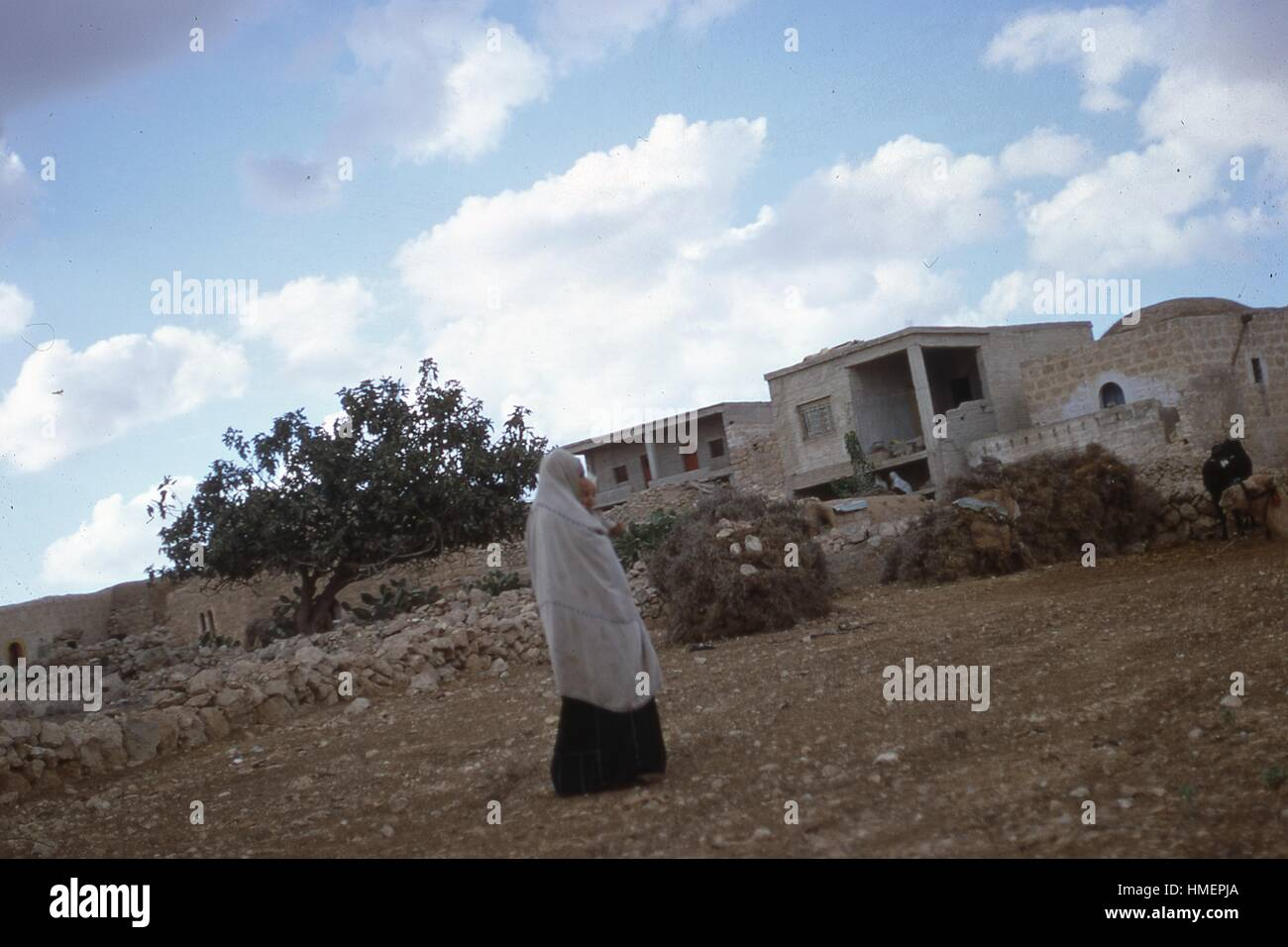 Arab woman wearing a niqab or burka carries a child while walking across rocky land toward houses and buildings - Stock Image
