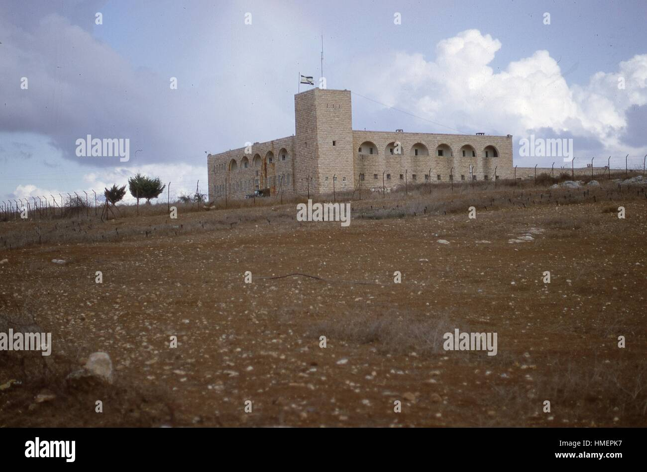 Landscape view from a distance of a stone fortification building with an Israeli flag flying, located behind a barbed - Stock Image