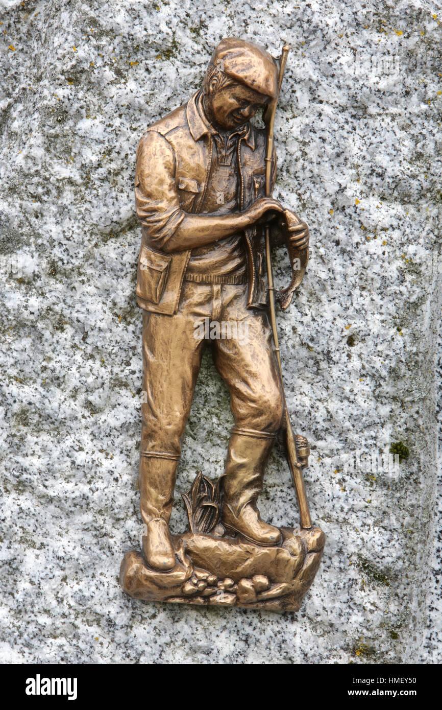 Sculpture d'un pêcheur sur une pierre tombale. - Stock Image