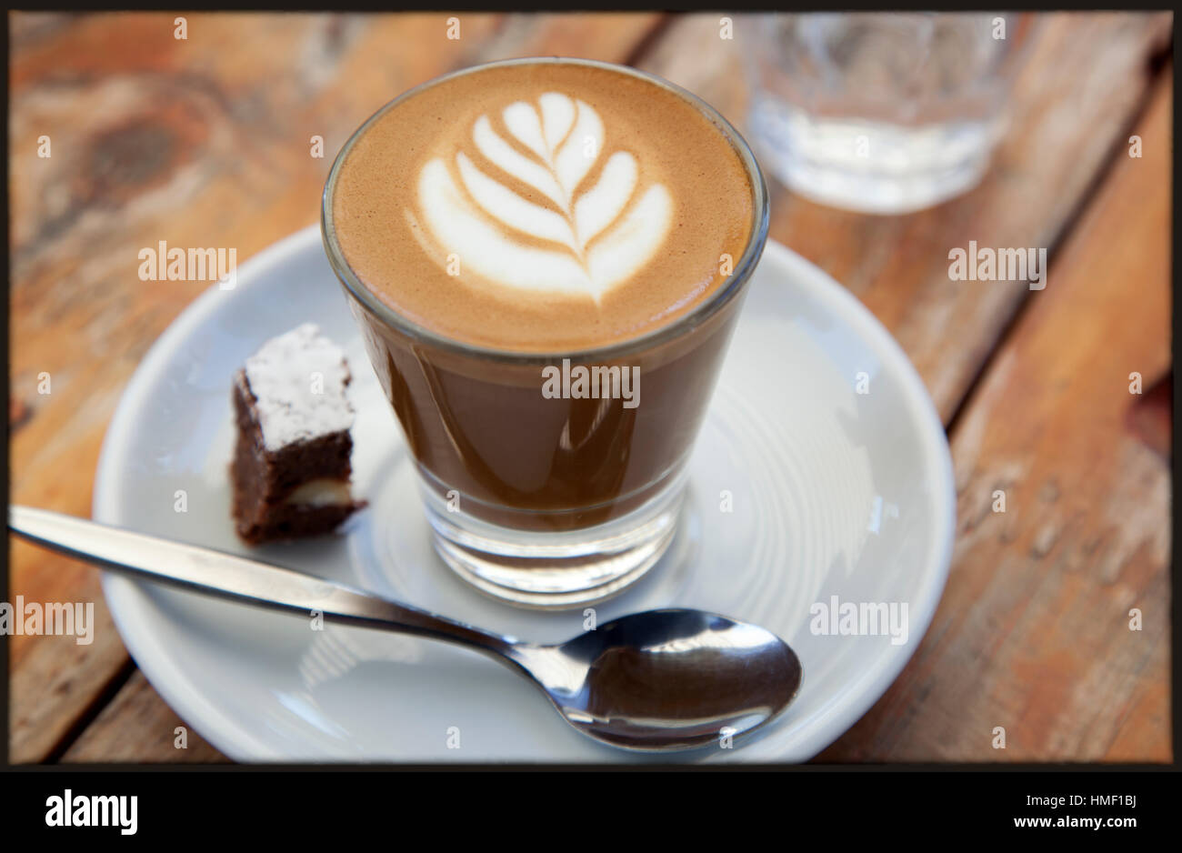 A perfectly made caffe macchiato and brownie on a cafe table outdoors - Stock Image