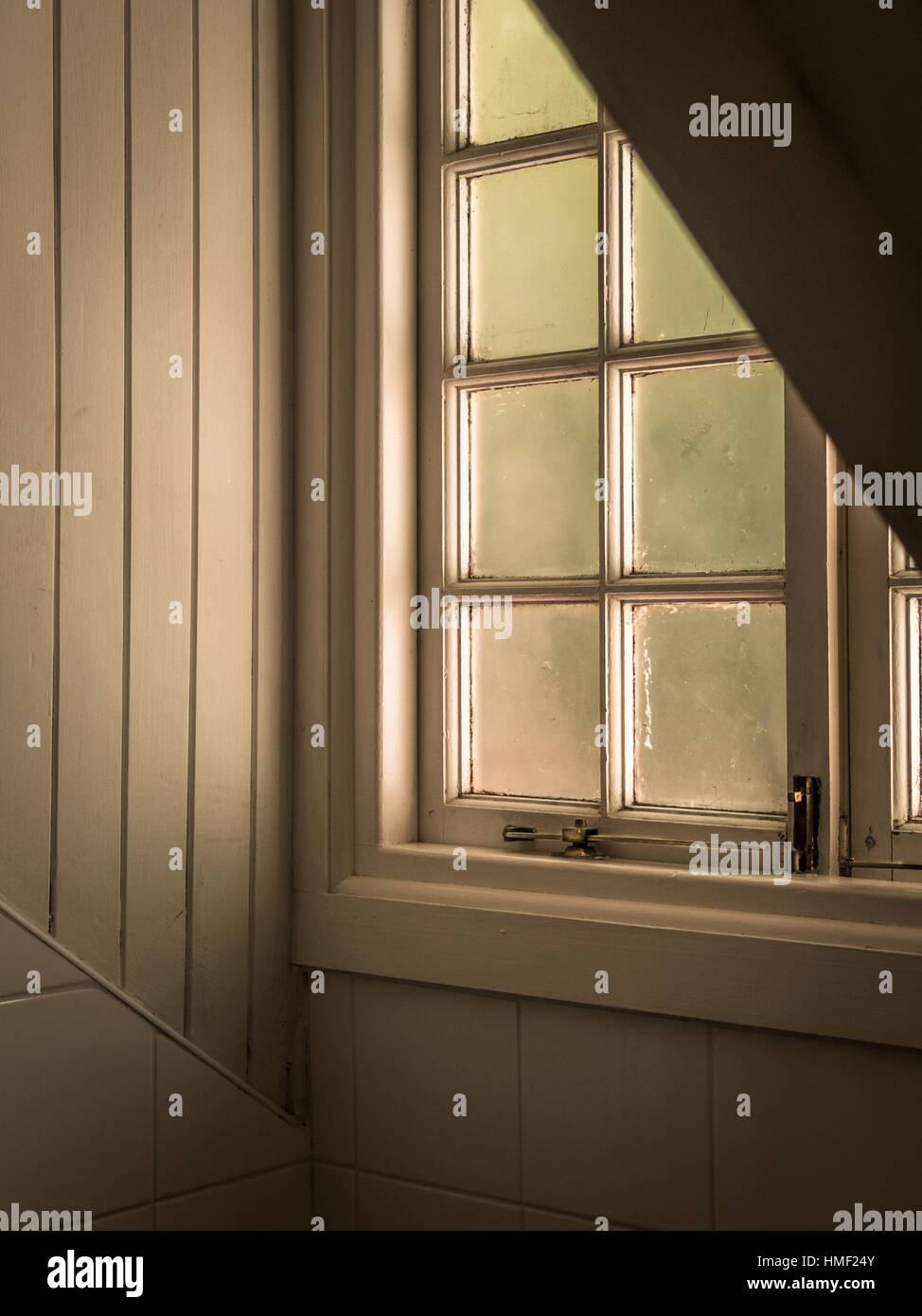 A loft window, frosted glass kjeeps out the glare. - Stock Image