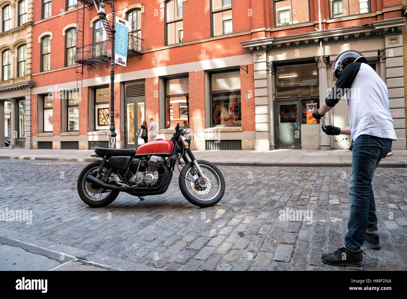 Soho, Manhattan, New York City, Man, 20-30, in Cycle Riding Helmet, stoping to photograph his Motor Cycle on his - Stock Image