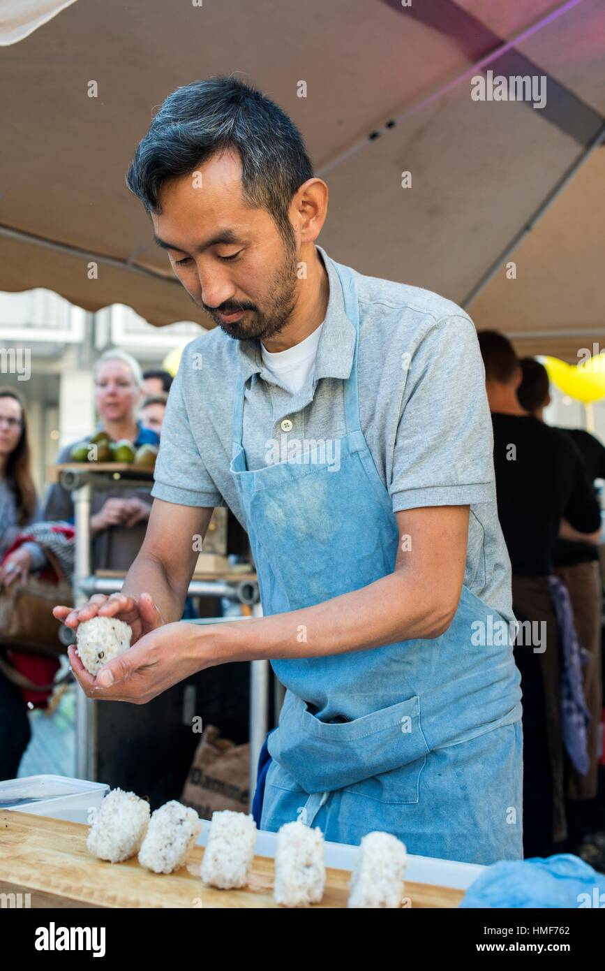 Rotterdam, Netherlands. Asian dude, producing a few rice dishes from his atall at World Food Day 2016. - Stock Image