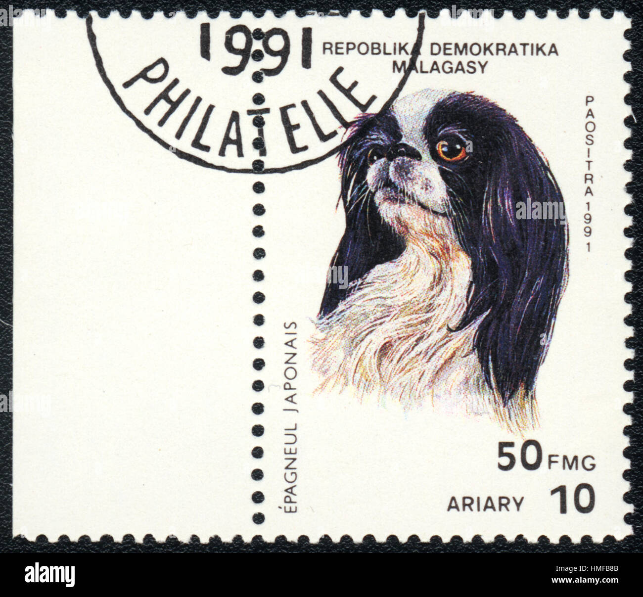 A postage stamp printed in Republica Malagasy shows a dog Japanese Chin, from series Breeds of dogs , circa 1991 Stock Photo