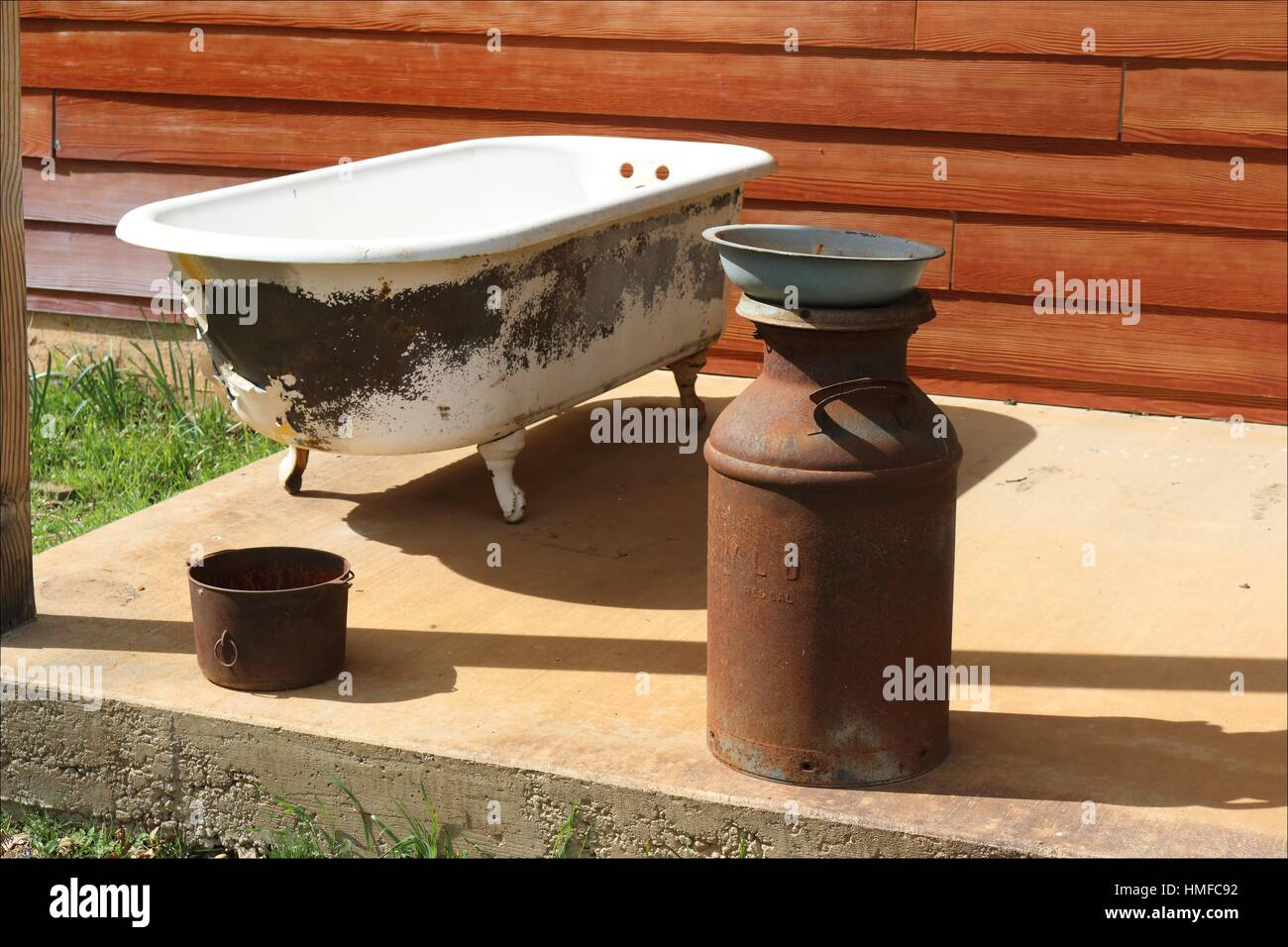 Old rusty antiques and an old claw foot tub decorate the porch of a home in Pleasant Valley, California, USA - Stock Image