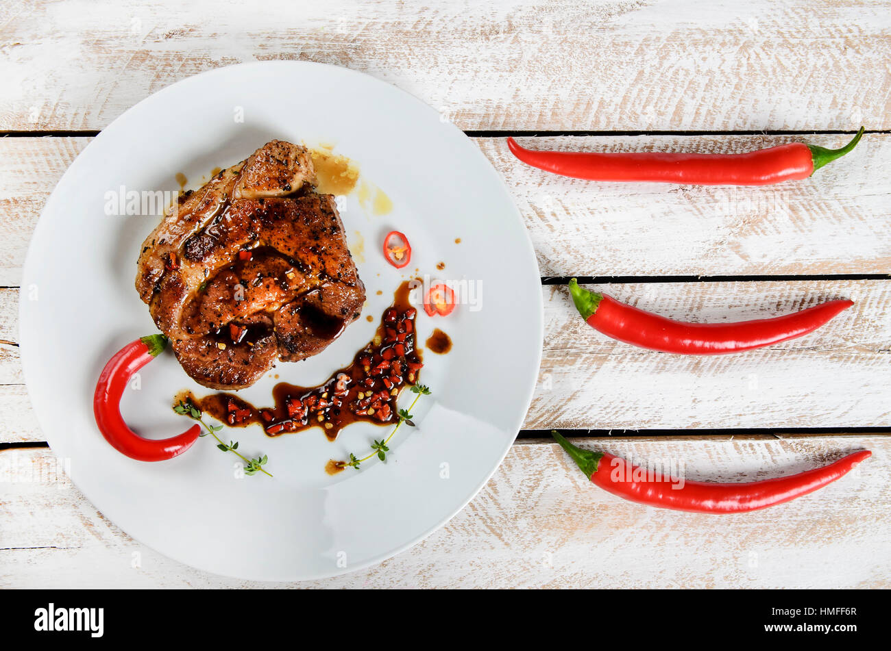meat with spices in a pan, rosemary, and hot chili peppers on a white wooden table background - Stock Image