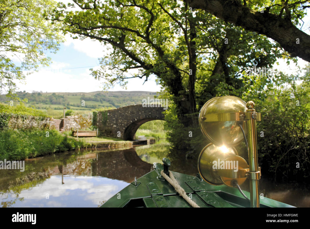 Sunlight shines on the brass headlamps of a canal barge in Wales. - Stock Image