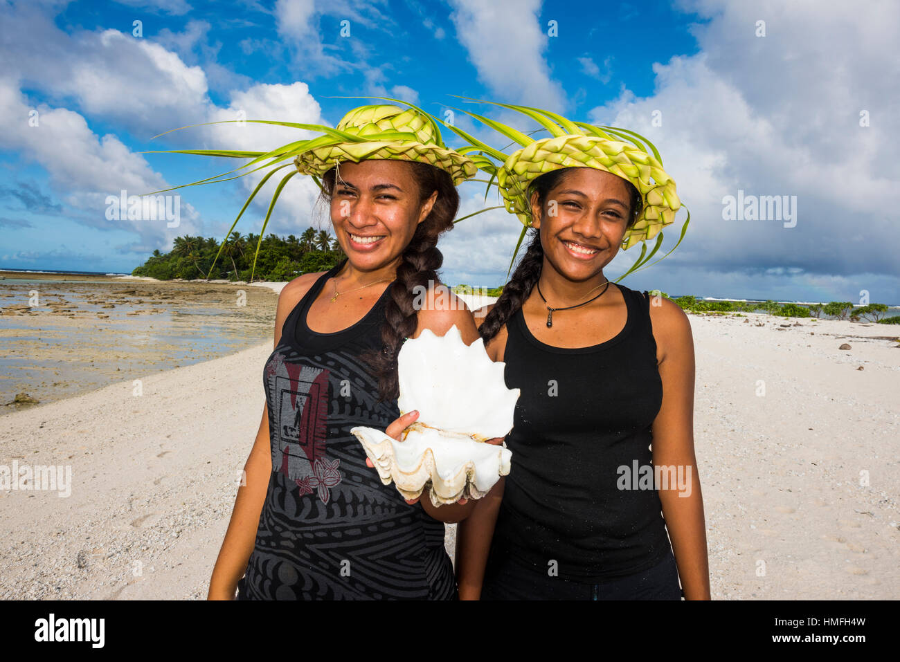 Local girls with palm leaves hats posing in the lagoon of Wallis, Wallis and Futuna, Pacific - Stock Image
