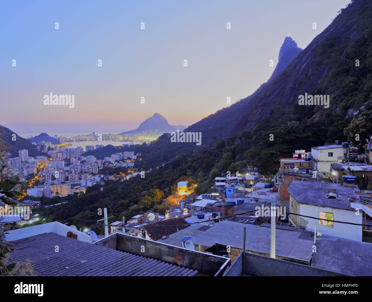 Twilight view of the Favela Santa Marta with Corcovado and the Christ statue behind, Rio de Janeiro, Brazil, South - Stock Image