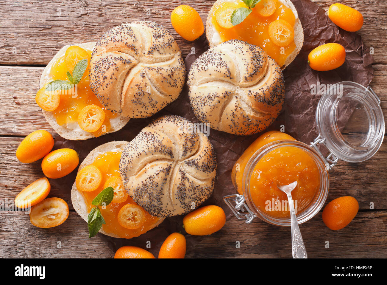 Sweet buns with kumquat jam and cream cheese close-up on the table. Horizontal view from above - Stock Image