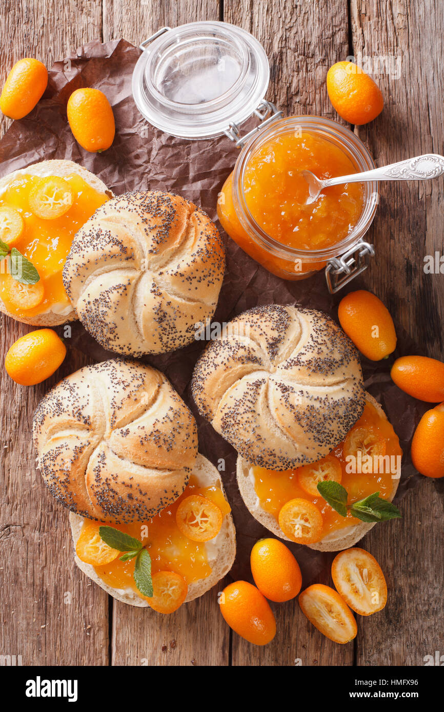 Sweet buns with kumquat jam and cream cheese close-up on the table. vertical view from above - Stock Image