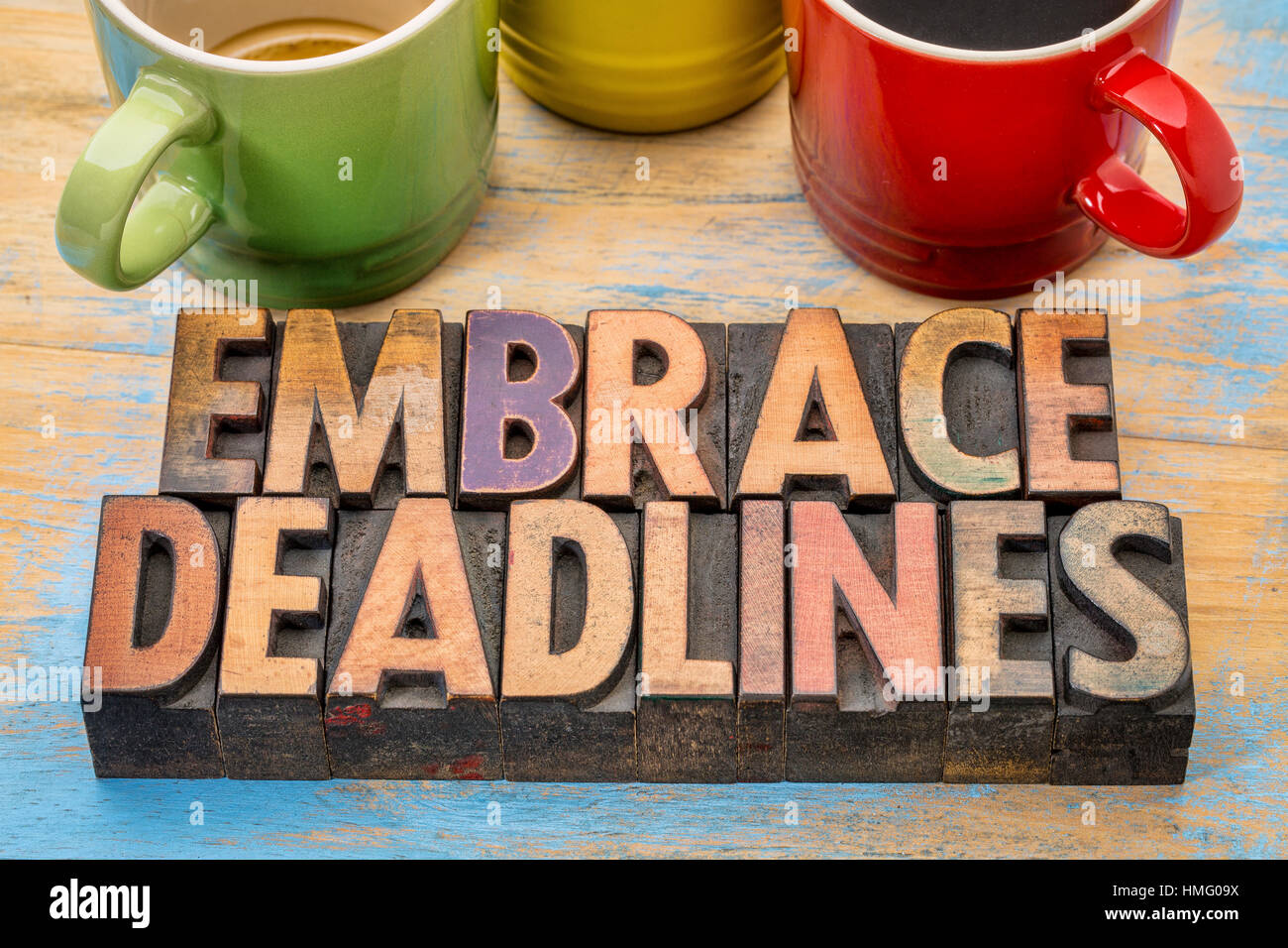 embrace deadlines - word abstract in vintage letterpress wood type blocks with cups of coffee - Stock Image
