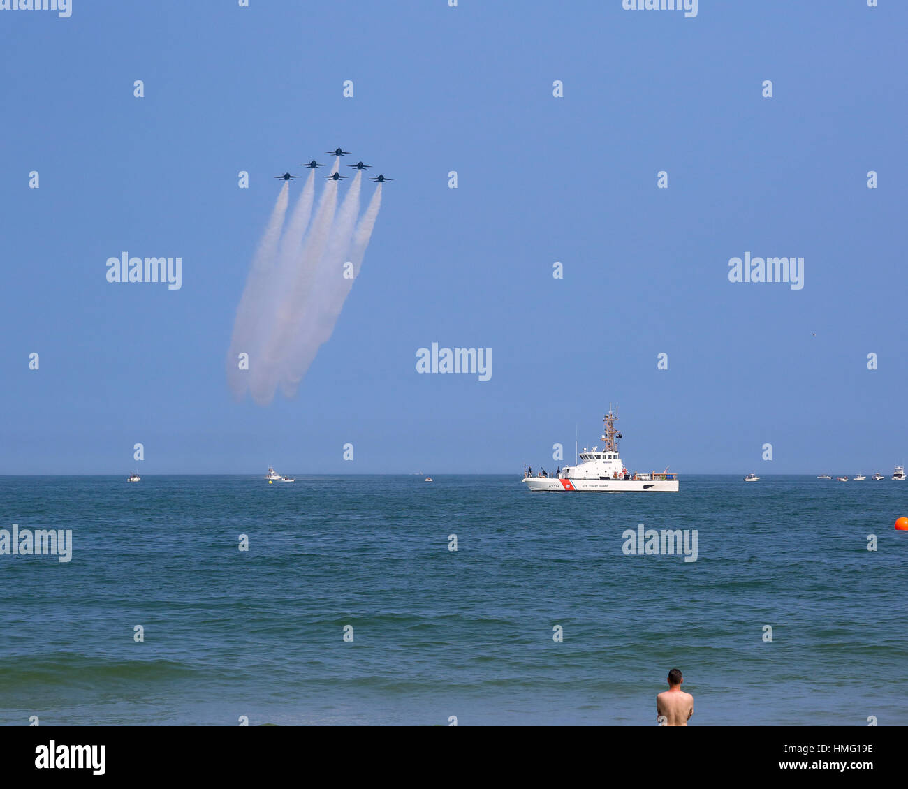 Six U.S. Navy Blue Angels F/A-18 aircraft in Delta Formation overflying USCGC Finback (WPB-87314) - Stock Image