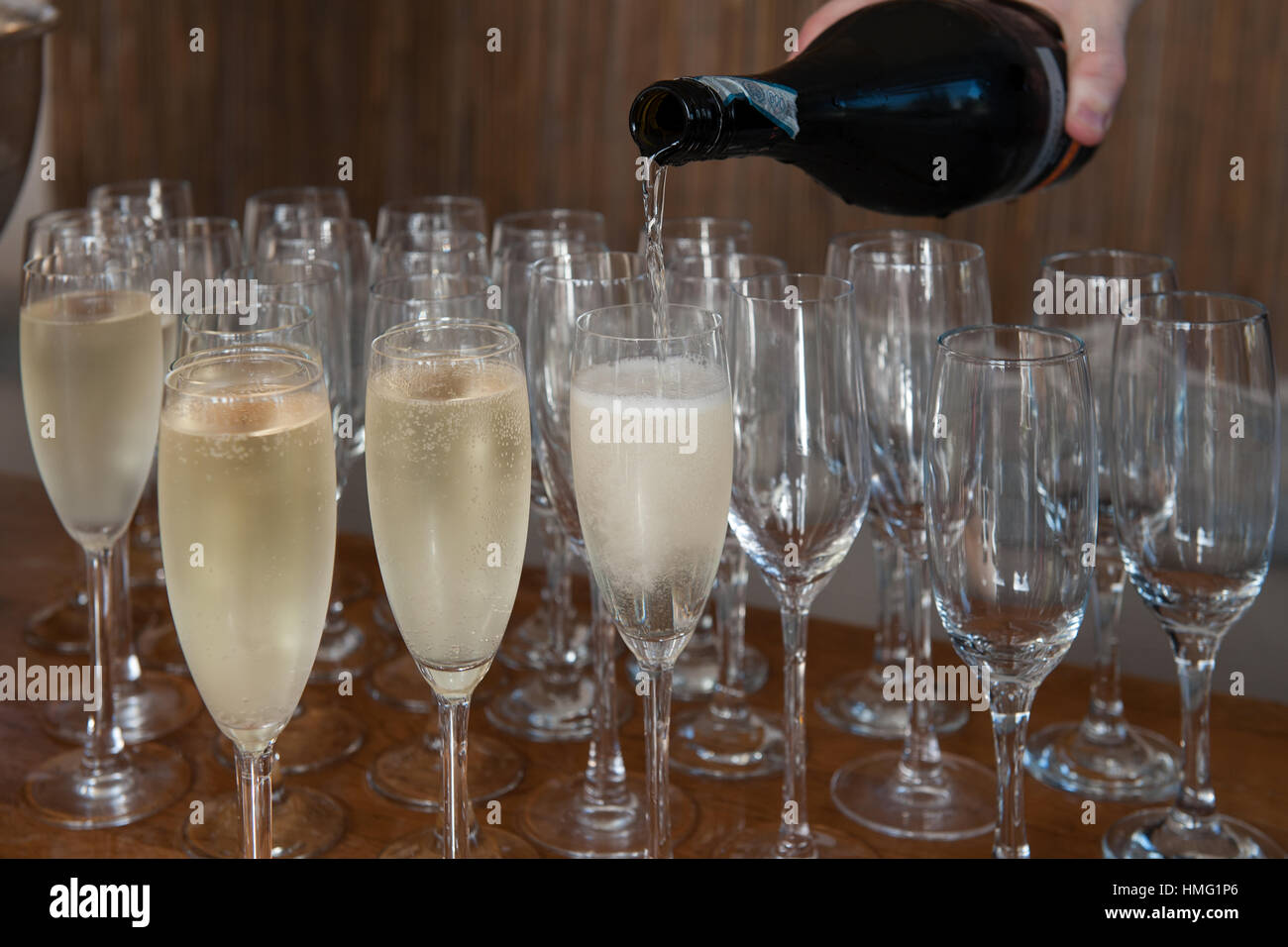 A closeup crop of a hand holding a prosecco bottle and pouring the prosecco into champagne flutes on a wooden table - Stock Image