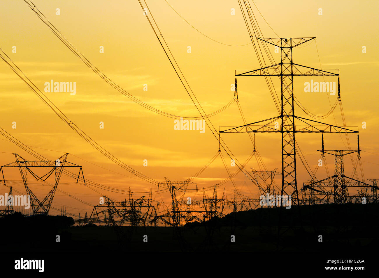 field of high voltage towers under dramatic sky - Stock Image