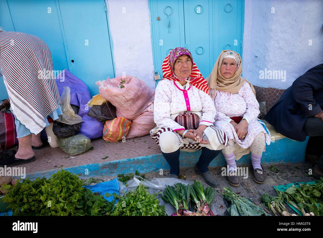 Two Moroccan women in traditional clothing selling vegetables in street market. Chaouen, Moroco Stock Photo